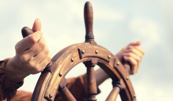 man steering a ships wheel