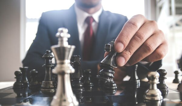 business man with chess pieces represents strategy