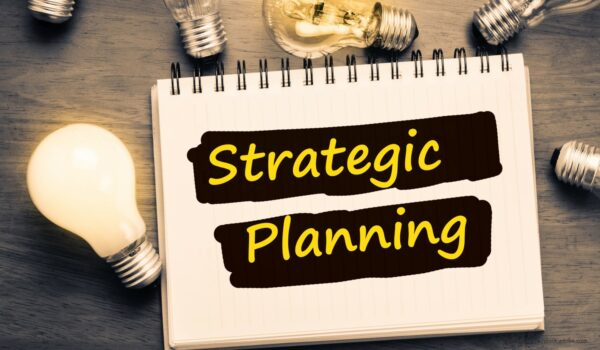 Notebook with Strategic Planning written with lightbulbs
