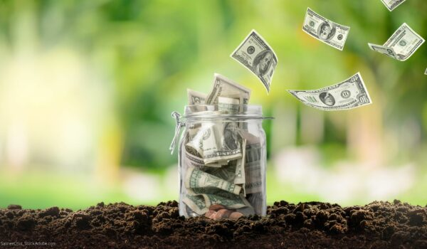 Mason Jar in dirt filled with money